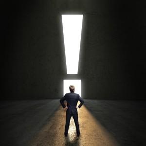 Geschftsmann steht vor einem leuchtenden Ausrufezeichen-Durchgang