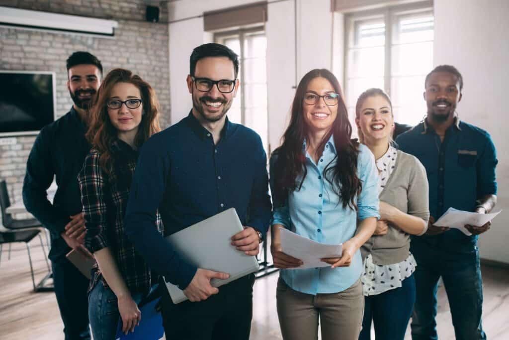 Mitarbeiterbindunf-Team-von-zufriedenen-Mitarbeitern-schauen-glücklich-in-die-Kamera