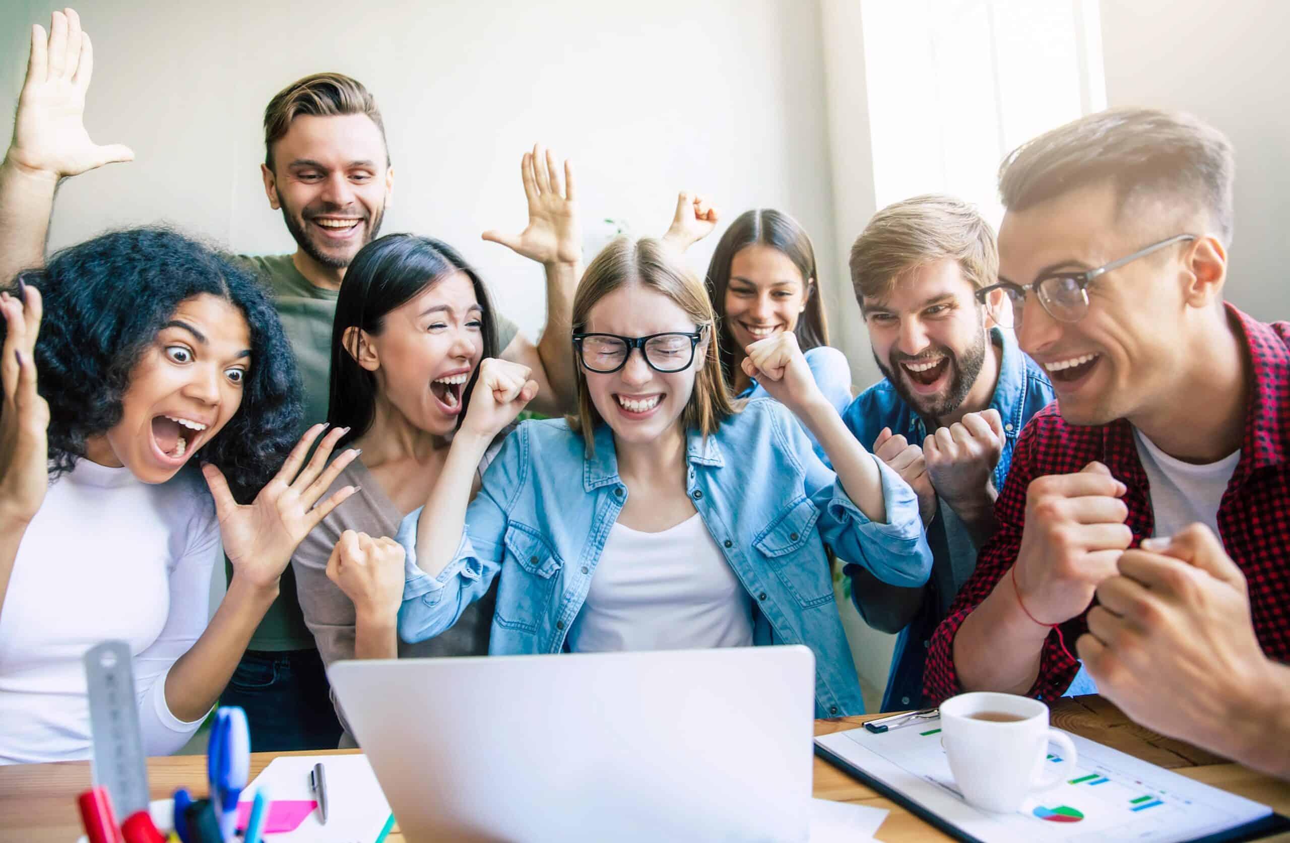 Team bon jungen Kollegen und Kolleginnen sitz vor einem Laptop und freut sich über einen Erfolg