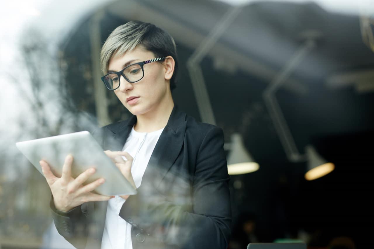 Frau mit Tablet an Fenster