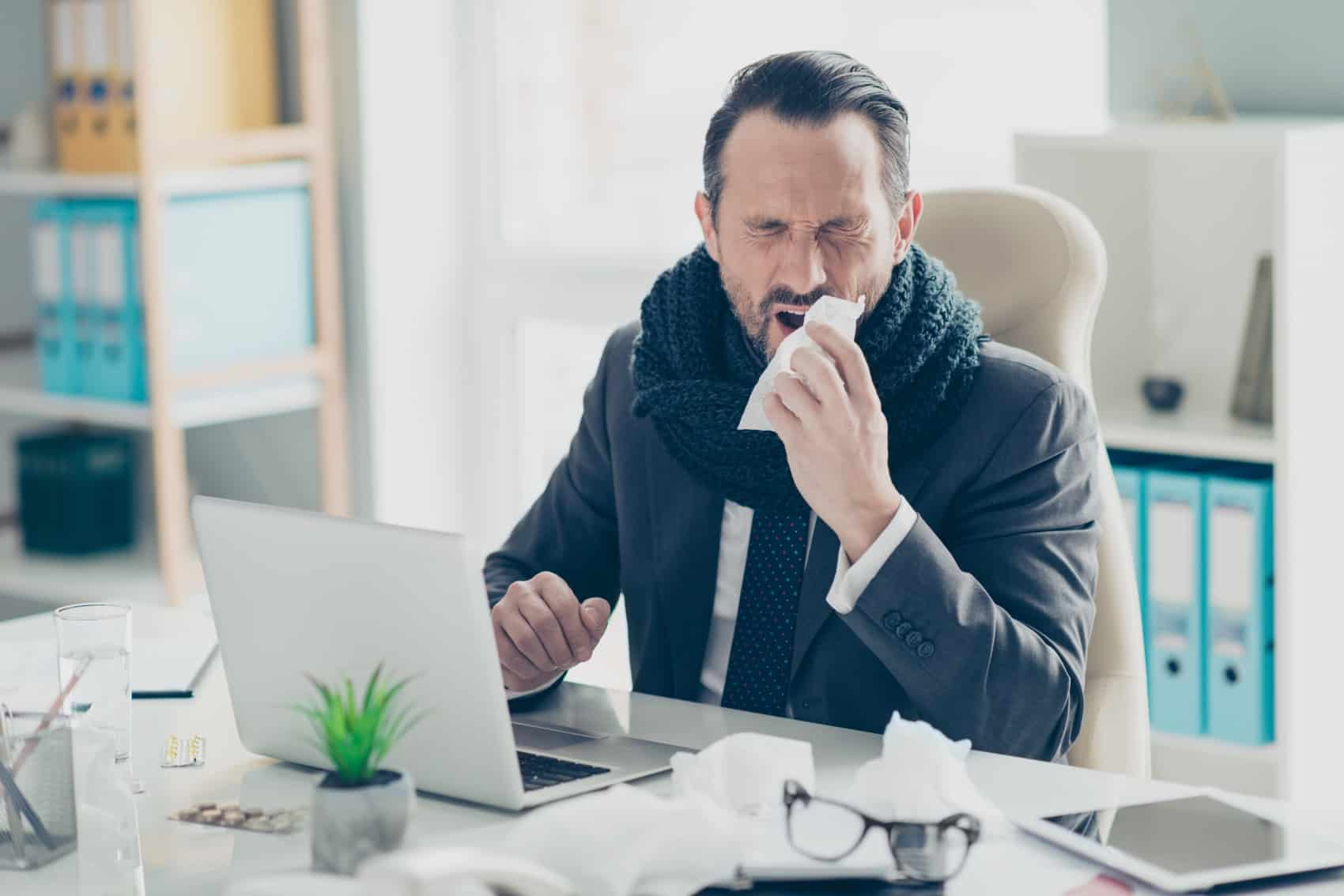 kranker Mann der im Büro sitzt