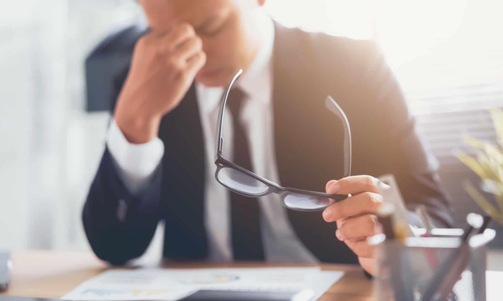 Businessmann im schwarzen Anzug mit Brille, der sich die Augen reibt